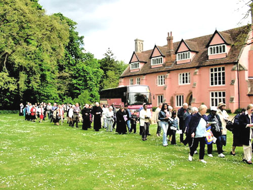 A pilgrim group prays in procession at Clare Priory, Suffolk, England